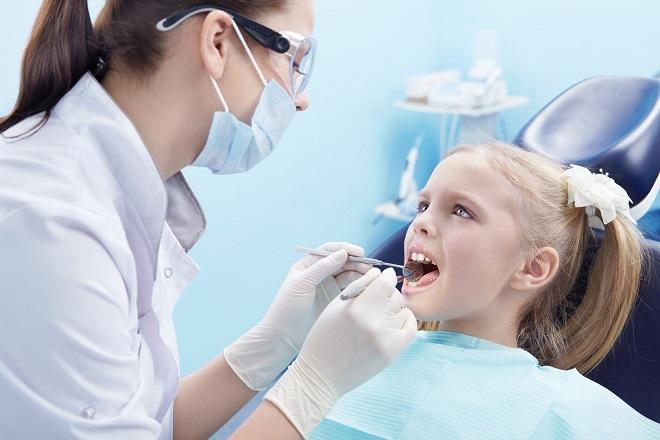 bác sĩ chữa răng cho bé gái