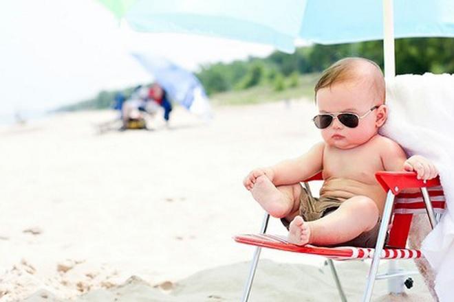bé ngồi nghỉ mát tránh nắng ở bãi biển