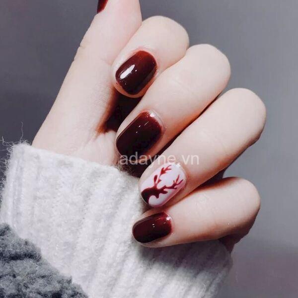 màu nail đỏ mận đẹp kết hợp họa tiết tuần lộc trên nền sơn móng trắng