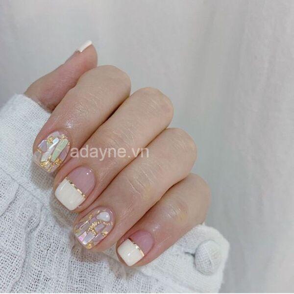 Nâng cao tính thẩm mỹ cho mẫu móng tay đẹp đính đá xà cừ với tone màu trắng kết hợp đường kẻ vàng gold bắt mắt