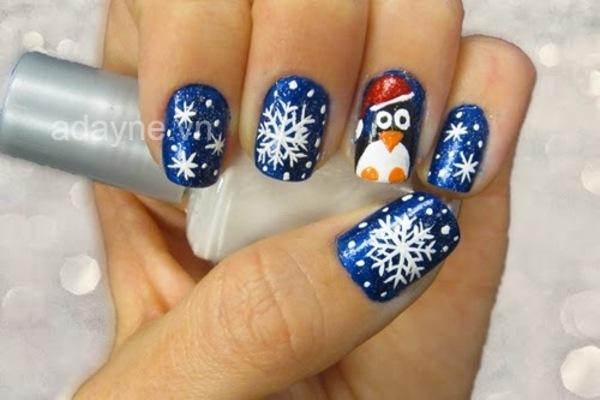 Mẫu nails noel bông tuyết trên gam màu xanh dương vừa cổ điển vừa hiện đại, điểm nhấn là họa tiết chim cánh cụt