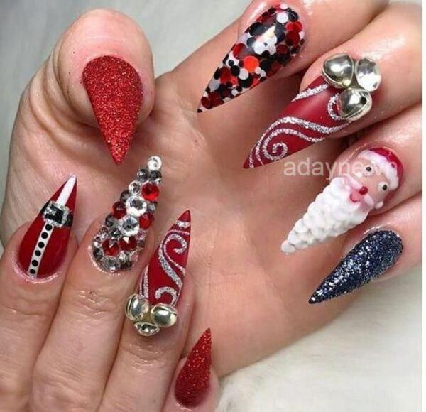 Sự kết hợp hoàn hảo giữa móng nhọn với tone sơn đỏ, họa tiết ông già noel 3D và đính đá cầu kỳ tạo nên mẫu nail noel cực kỳ độc lạ