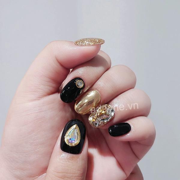 Tone màu đen kết hợp màu vàng gold sang chảnh, nhấn nhá thêm vài viên đá cho ra đời mẫu nail tết nổi bần bật