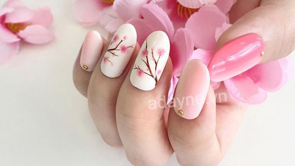 Kiểu dáng đơn giản họa tiết hoa nhấn nhá hạt kim loại cũng là một sự lựa chọn cho mẫu nail Tết đẹp miễn chê