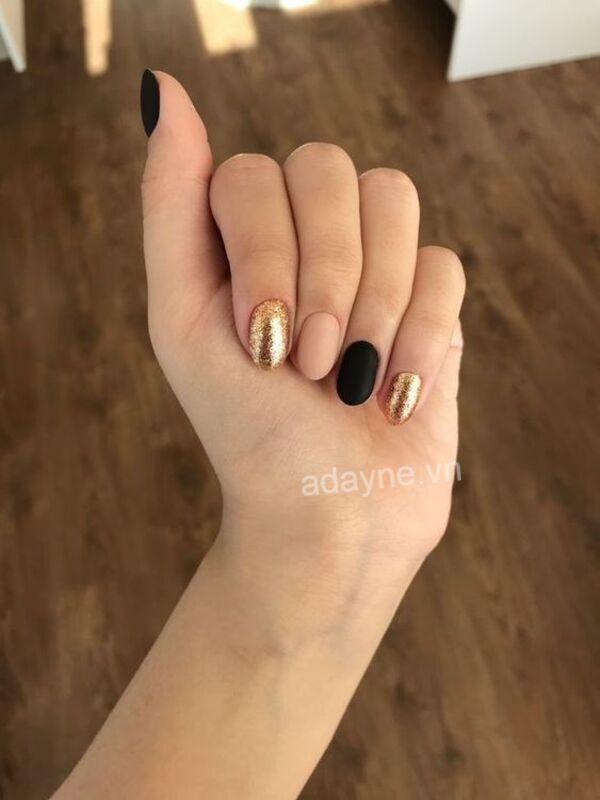 Vàng ánh kim kiêu sa kết hợp với tone màu đen nhám tạo hiệu ứng tương phản cho mẫu nail Tết nổi bần bật