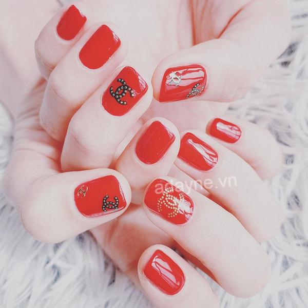 Mẫu nail Tết tone đỏ móng vuông hiện đại kết hợp họa tiết Chanel sang chảnh mang lại vẻ đẹp kiêu sa