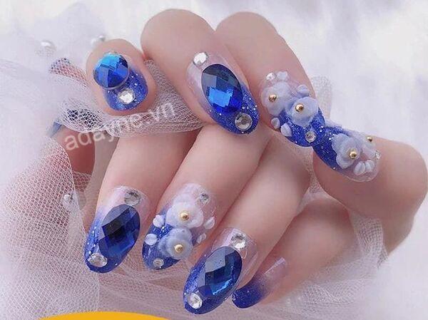 Mẫu nail đơn giản sang trọng đính đá màu xanh dương và họa tiết hoa trắng kiêu sa