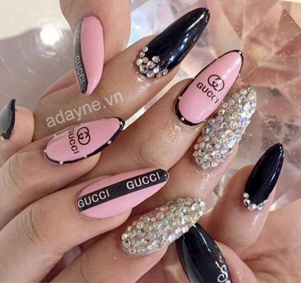Mẫu nail gucci đẹp tone hồng đen kết hợp đính đá và vẽ họa tiết logo vừa nổi bật vừa ngọt ngào, sang chảnh