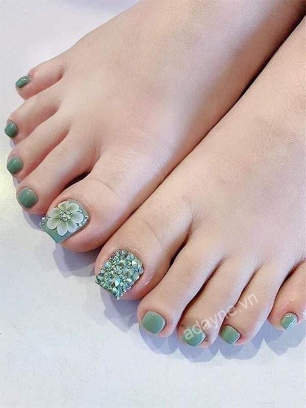Sơn móng chân màu xanh rêu họa tiết hoa nổi kết hợp đính đá rất đáng để thử một lần