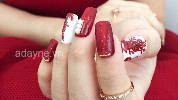 Móng tay đính đá đẹp màu đỏ này không chỉ tiệp với màu của hoa cưới, làm điểm nhấn cho màu váy cưới tinh khôi mà còn rất phù hợp cho các nàng dâu mệnh Hỏa