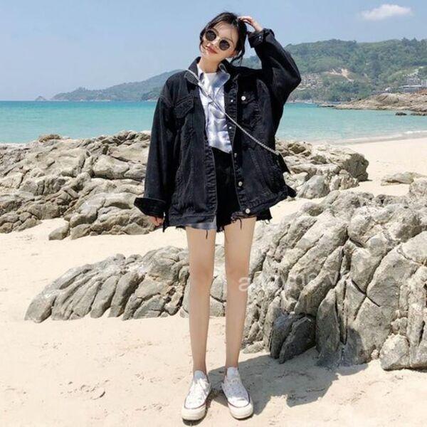 Phối đồ với áo khoác jean đen nữ form rộng cùng áo thun trắng và quần short đen khoe đôi chân dài miên man