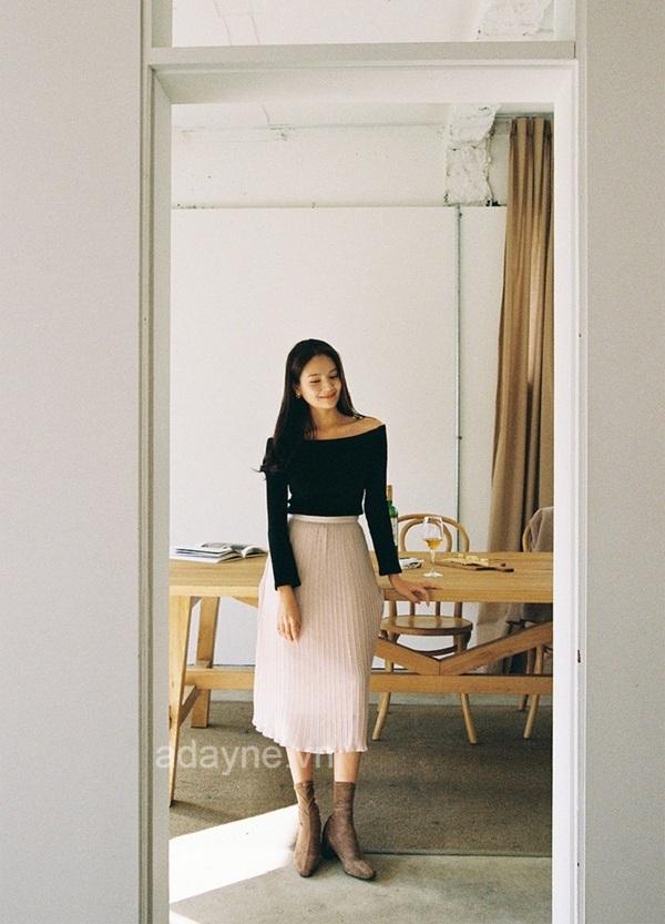 Hóa thân thành nàng thơ nhẹ nhàng, tinh tế với kiểu phối đồ chân váy dài trắng xếp ly với áo thun dài tay trễ vai màu đen và boot dáng thấp